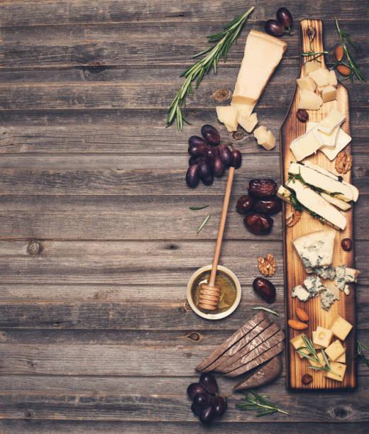 Käseauswahl auf Holzbrett rustikal. Käseplatte mit verschiedenen Käsesorten, Trauben, Nüssen, Honig und Termine auf verwittertem Holz Hintergrund. – Foto