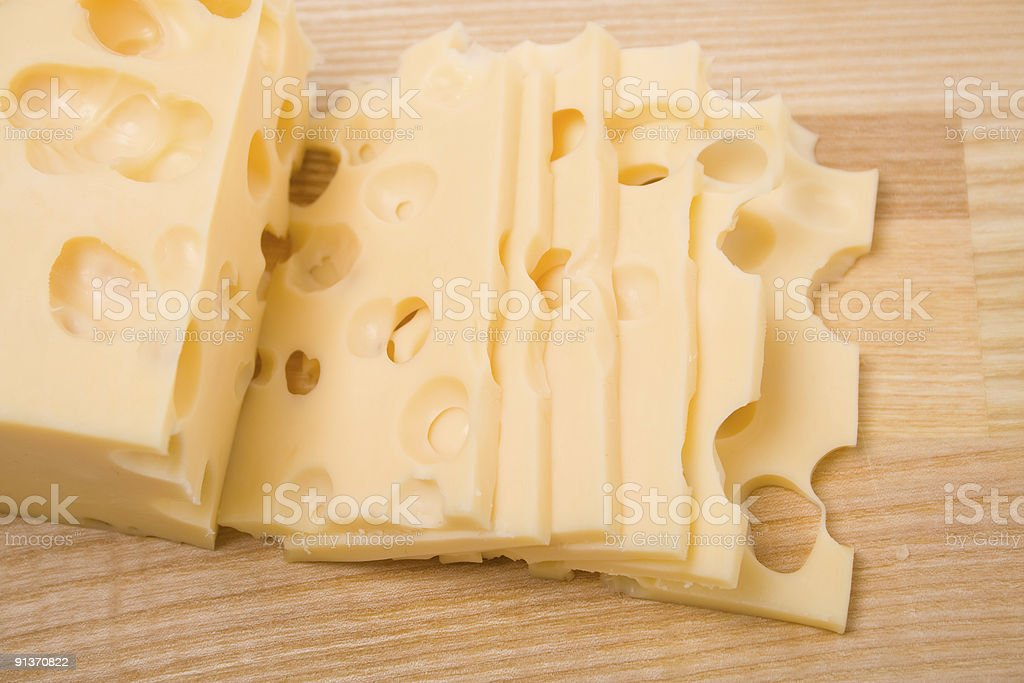 Cheese slices on cutting board stock photo