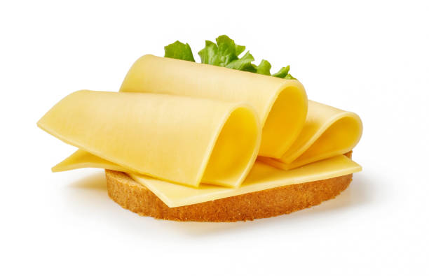 cheese slices with salad leaf on piece of bread. sandwich isolated on white background. - maasdam foto e immagini stock