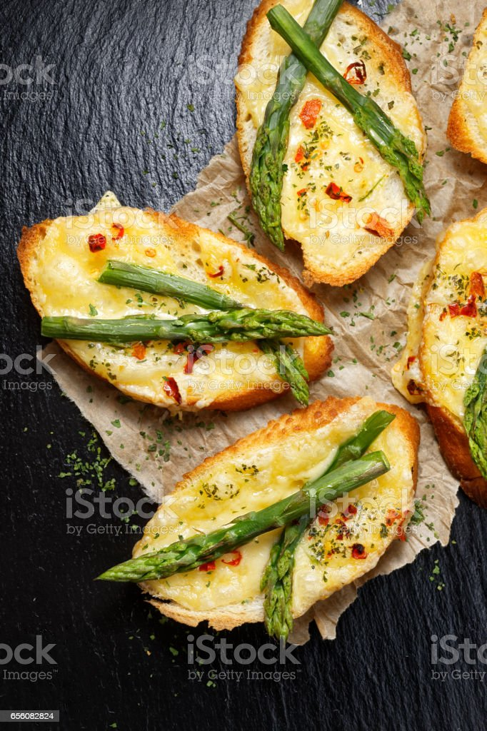 Cheese toasts with asprgus and chili flakes stock photo