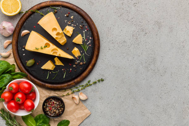 cheese, tomatoes and fresh herbs on concrete background. - maasdam foto e immagini stock