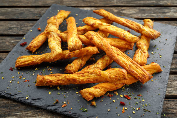 cheese twist, sticks, snack with herbs on stone board - twisted stock pictures, royalty-free photos & images