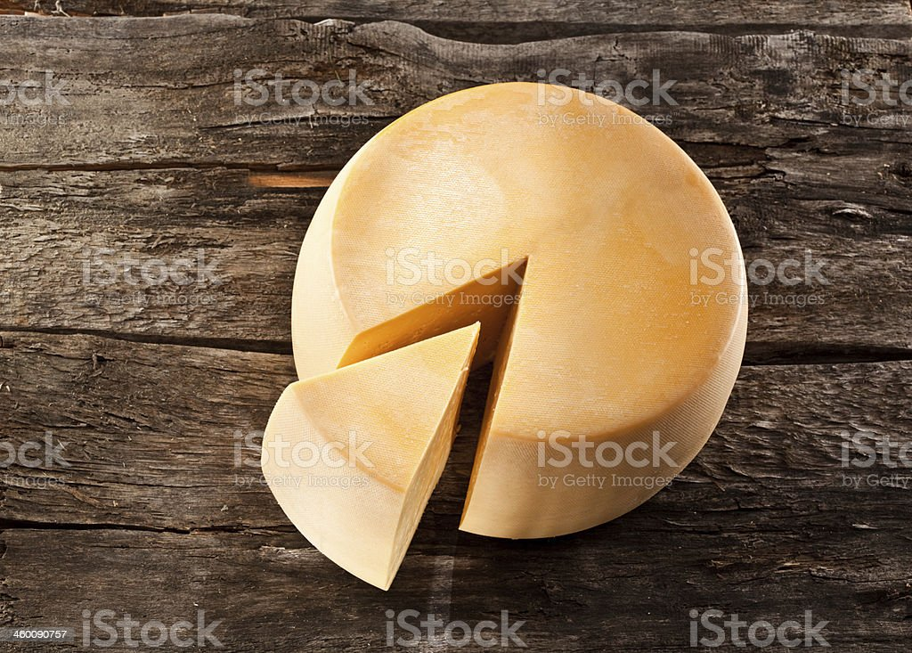 Cheese wheel on wooden table royalty-free stock photo