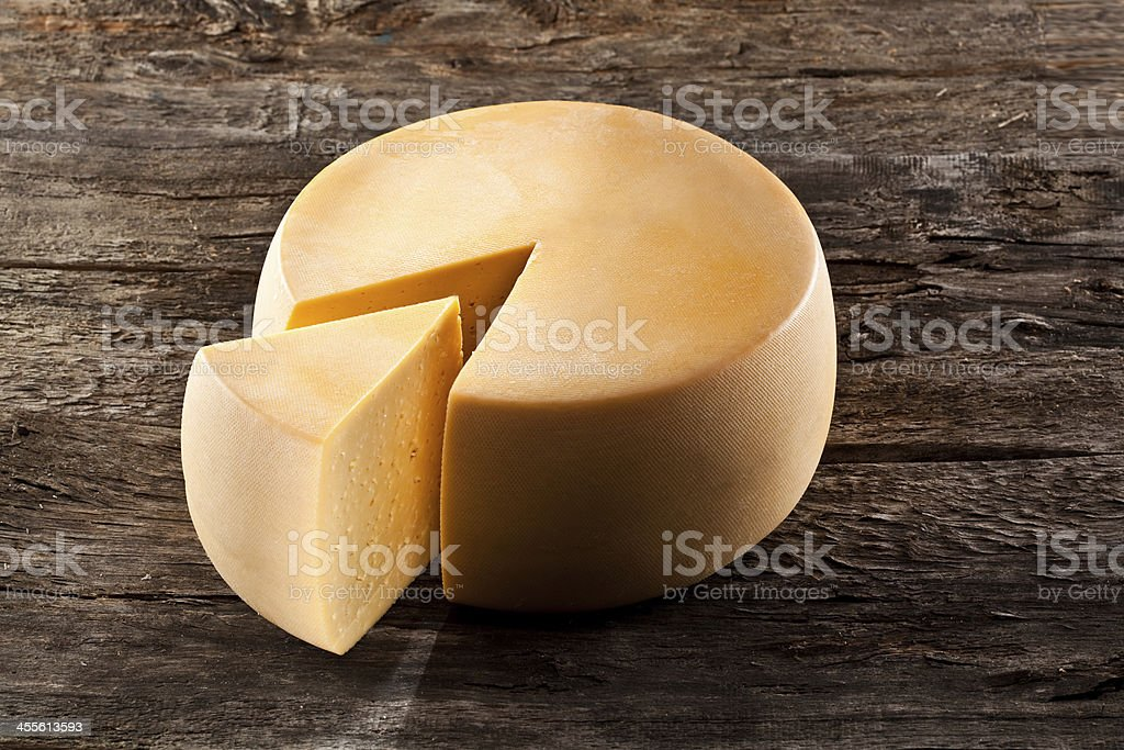 Cheese wheel on wooden table with wedge cut out stock photo