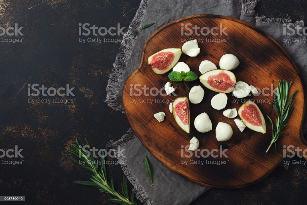Cheese with figs on a cutting board. Copy space, top view. stock photo