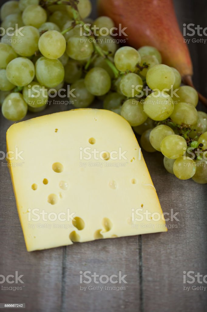 Cheese with grapes and pear on wooden tray stock photo