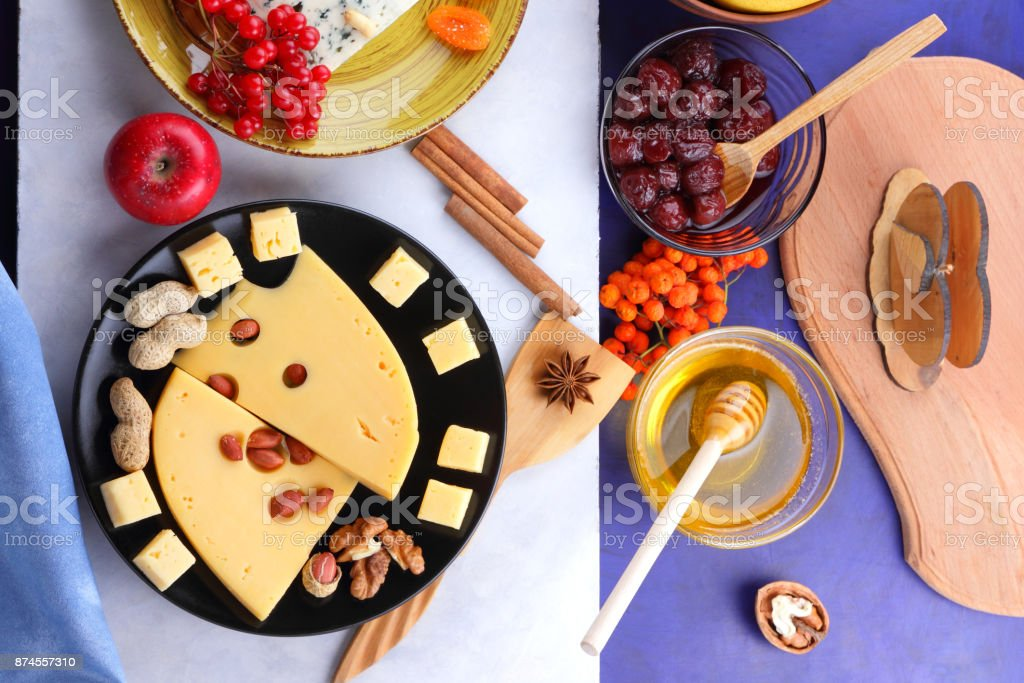 Cheese with mold, fruit, hard cheese with holes on a dark blue background, cheese on a black plate, fruits, nuts, honey, jam, Christmas dinner, multicolored background, retro style stock photo