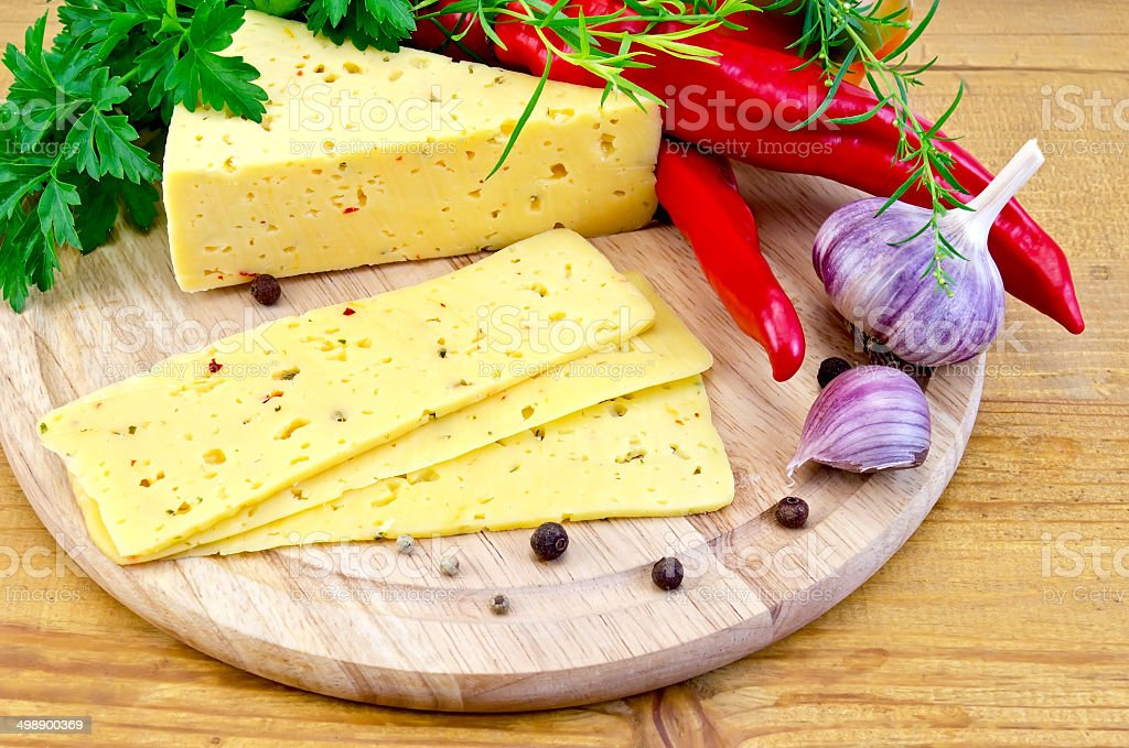 Cheese with spices and herbs on a round board royalty-free stock photo
