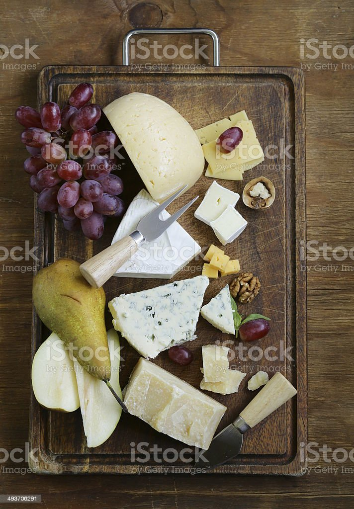 cheeseboard with assorted cheeses (parmesan, brie, blue, cheddar) stock photo