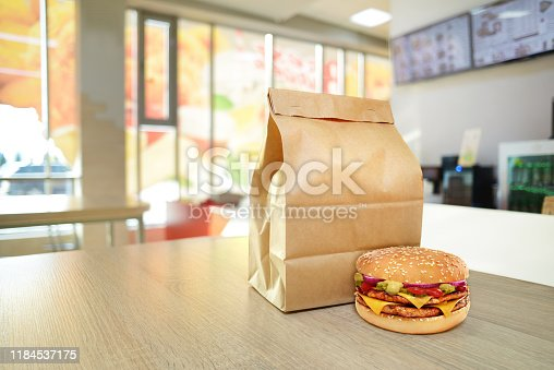 Cheeseburger and craft paper bag on wooden counter of cafe. Take out food concept. To go package mock-up
