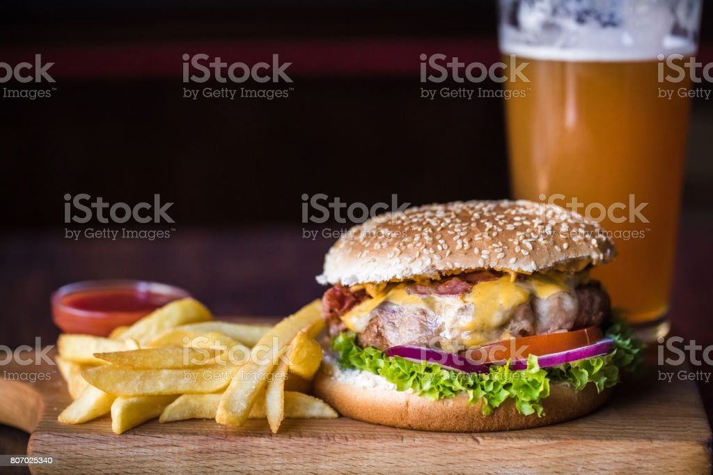 Cheeseburger and fries on restaurant table stock photo