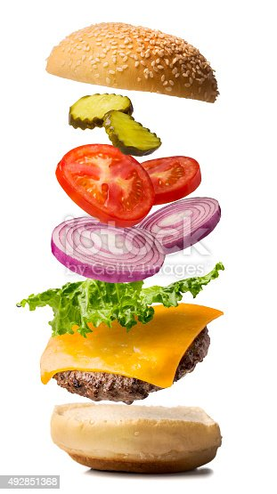 A cheeseburger being dropped into place.  The cheeseburger exploded view contains lettuce, red onion, tomato, and pickle with the bun top falling into place.  The photograph is on pure white for easy compositing.  Please see my portfolio for other food images.