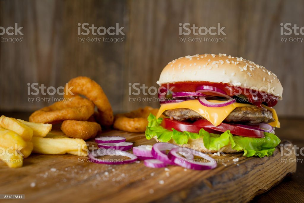Cheeseburger, french fries and onion rings on wooden chopping board over wooden backdrop stock photo