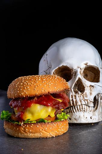 Cheeseburger next to a human skull