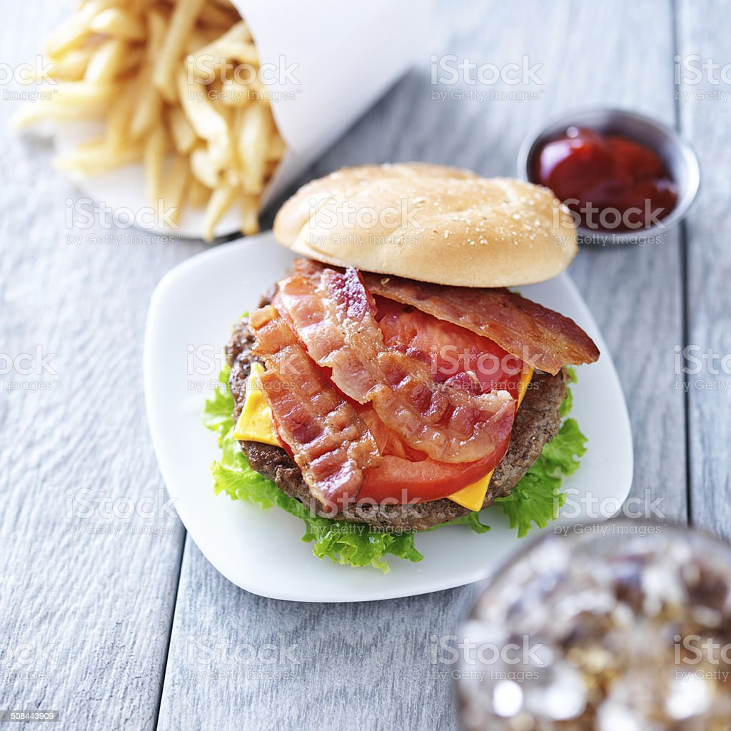 cheeseburger with bacon and bun to the side stock photo