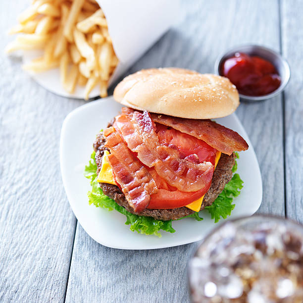 cheeseburger with bacon and bun to the side cheeseburger with bacon and french fries shot overhead with bread bun off to the side bacon cheeseburger stock pictures, royalty-free photos & images