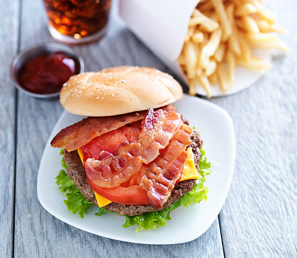 cheeseburger with bacon cheeseburger with bacon and french fries shot overhead and bread bun off to the side bacon cheeseburger stock pictures, royalty-free photos & images