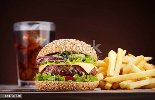 fresh cheeseburger with glass of cola and pile of french fries on wooden table