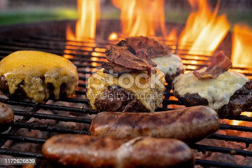 Cheeseburgers and Brats on a Fiery Charcoal Grill with Flames