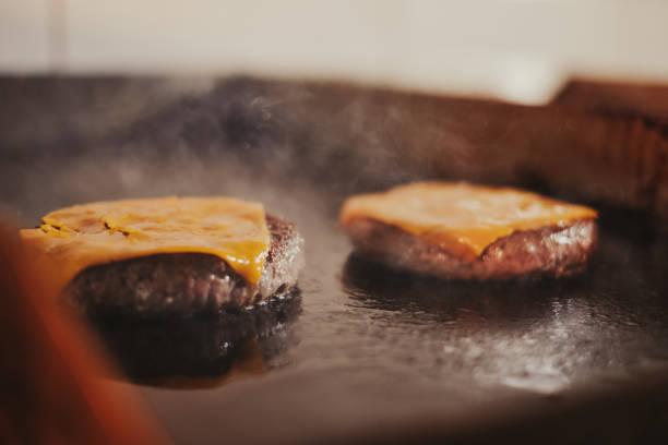 Hamburguesas con queso friendo en la parrilla - foto de stock