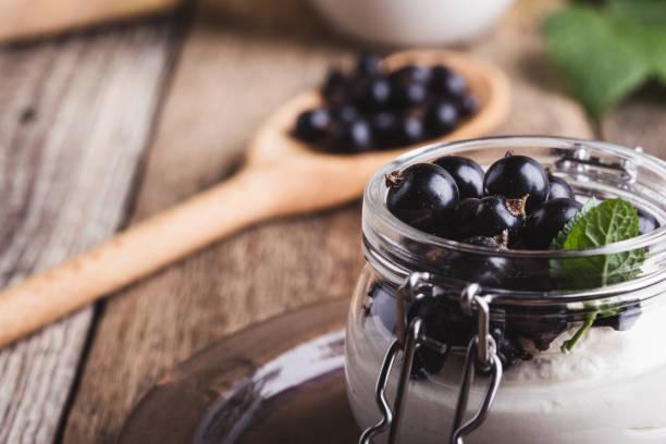 Käsekuchen-Crème-Parfaits mit frischen schwarzen Johannisbeeren in Glas – Foto