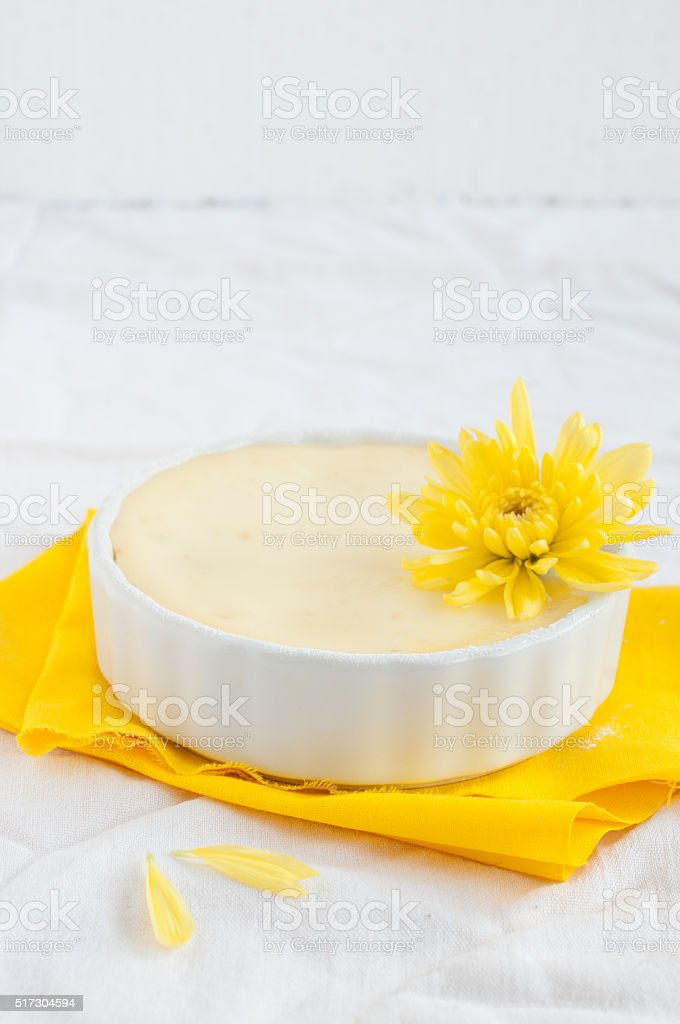 Cheesecake in ceramic bowl with yellow flowers stock photo