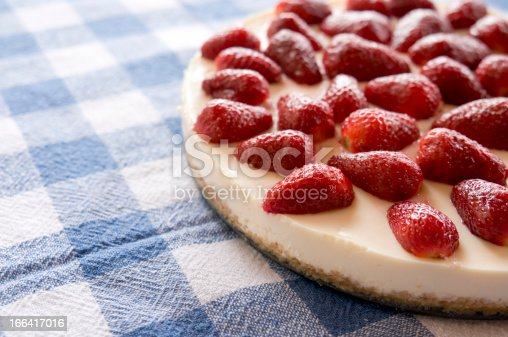 homemade lemon cheesecake with strawberries on the table
