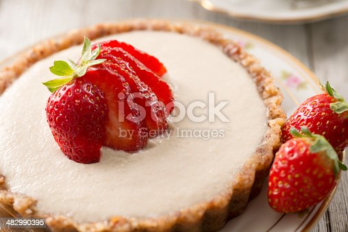 Delicious vegan cheesecake with strawberry slices and a nut crust.