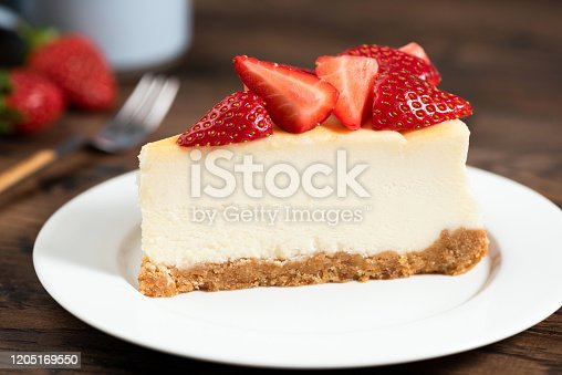 Cheesecake slice with strawberries. Plain New York Classical Style cheesecake on white plate closeup view