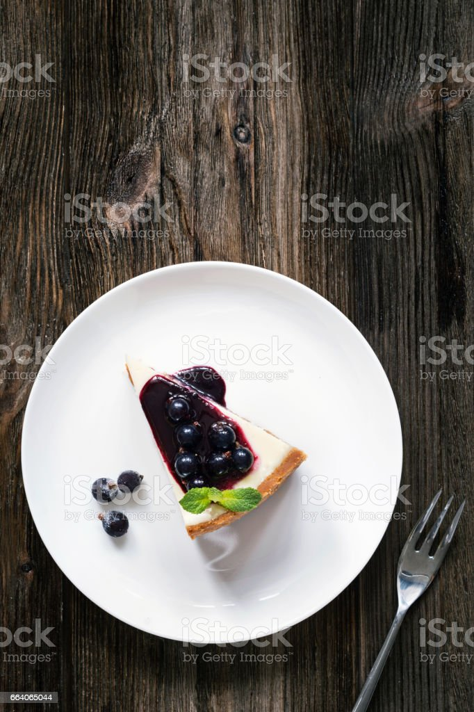 Cheesecake with blueberry sauce on white plate. Table top view stock photo