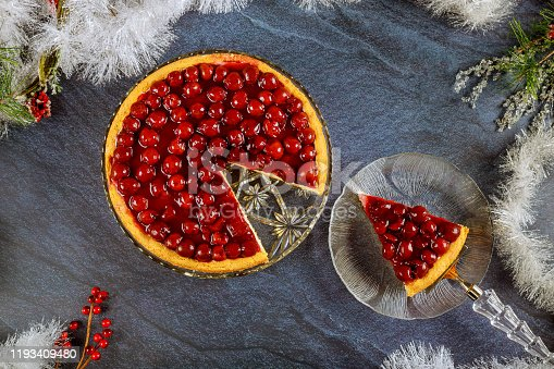 Cheesecake with cherry topping and christmas decoration. Top view.