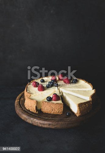 istock Cheesecake with fresh berries on cutting board on dark background 941400022