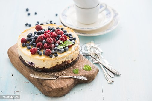 istock Cheesecake with fresh raspberries and blueberries on a wooden serving 498200670