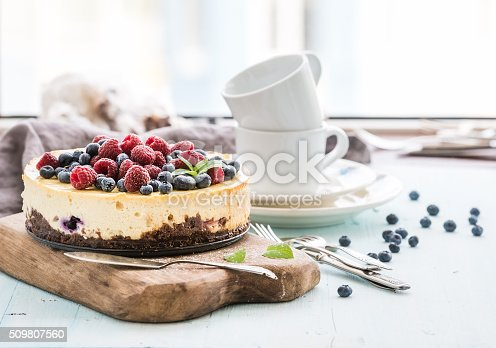 istock Cheesecake with fresh raspberries and blueberries on a wooden serving 509807560