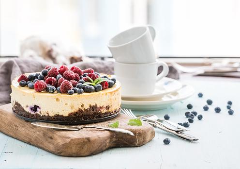 Cheesecake with fresh raspberries and blueberries on a wooden serving