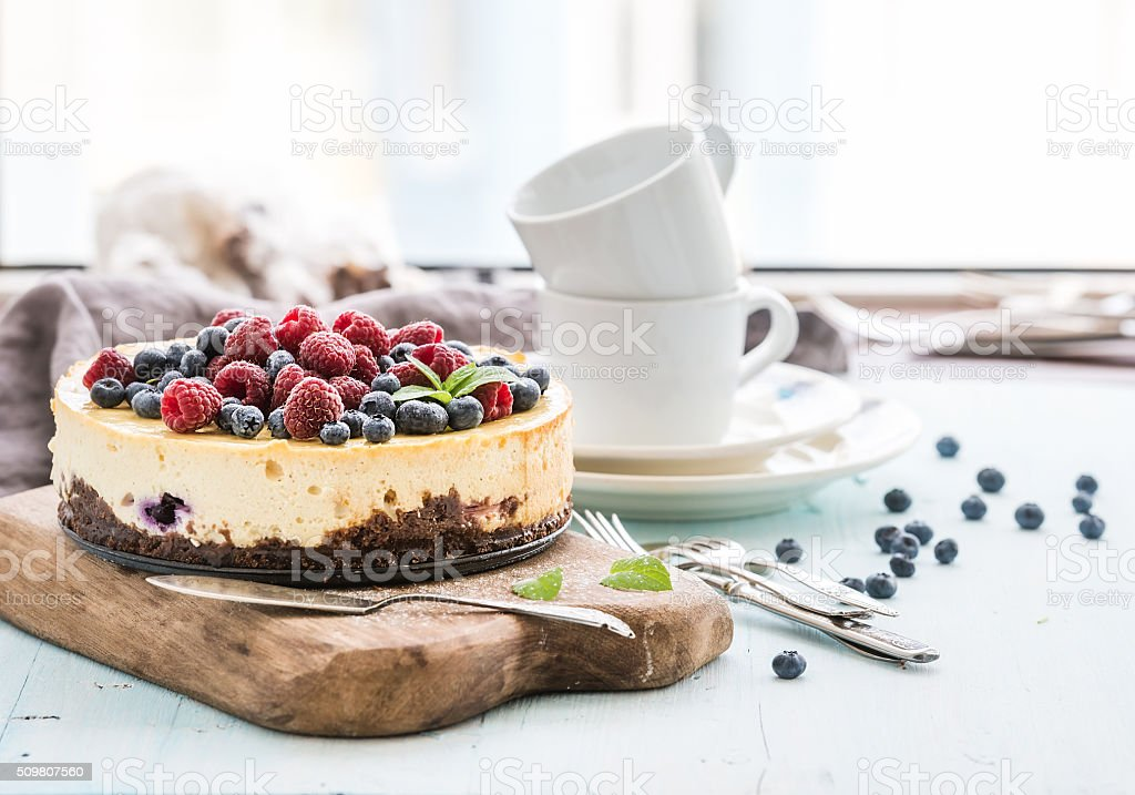 Cheesecake with fresh raspberries and blueberries on a wooden serving stock photo