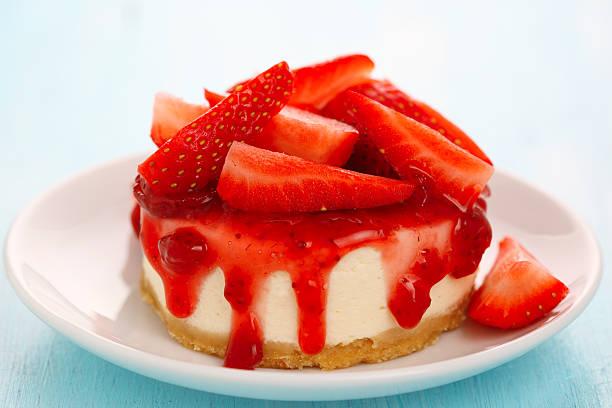 Cheesecake with fresh strawberries on white plate closeup stock photo