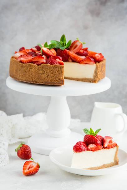 käsekuchen mit frischen erdbeeren auf weißen kuchen stehen - käsekuchen kekse stock-fotos und bilder