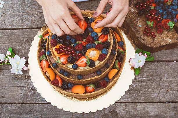 käsekuchen mit obst und beeren - orange hochzeitstorten stock-fotos und bilder