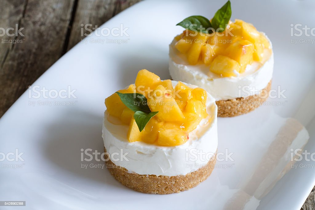 Cheesecake with peaches on wooden background.
