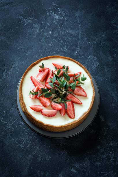 käsekuchen mit erdbeeren auf dunklem steintisch - obst käsekuchen stock-fotos und bilder