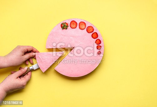 Woman slicing a strawberry cheesecake slice, on a yellow seamless background. Serving a no-bake cheese cake with red berries. Summer fruity pie.