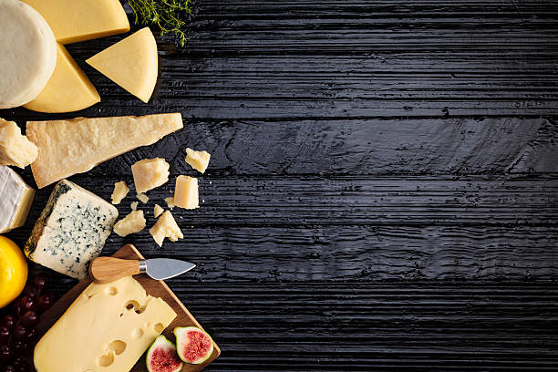 Cheeses on dark table stock photo
