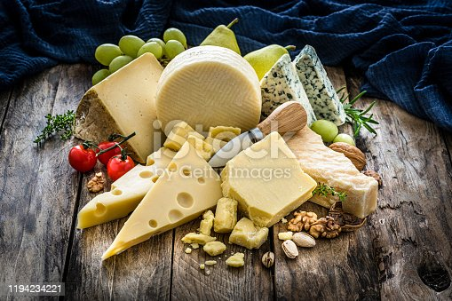 Wooden table with a delicious variety of cheeses. Cheeses included in the composition are Manchego cheese, goat cheese, emmental cheese, Roquefort cheese, Parmesan cheese and Cheddar cheese. Predominant colors are yellow and brown. High resolution 42Mp studio digital capture taken with Sony A7rii and Sony FE 90mm f2.8 macro G OSS lens