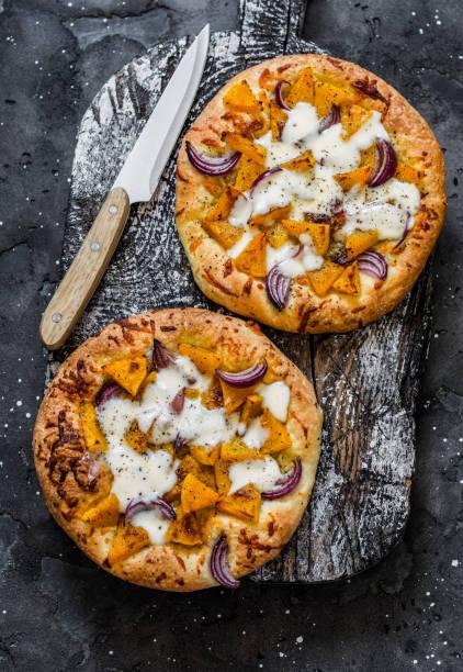 Cheesy Herbst veggie Fladenbrot. Kürbis, Süßkartoffel, rote Zwiebel, Mozzarella Pizza auf dunklem Hintergrund, Ansicht von oben – Foto