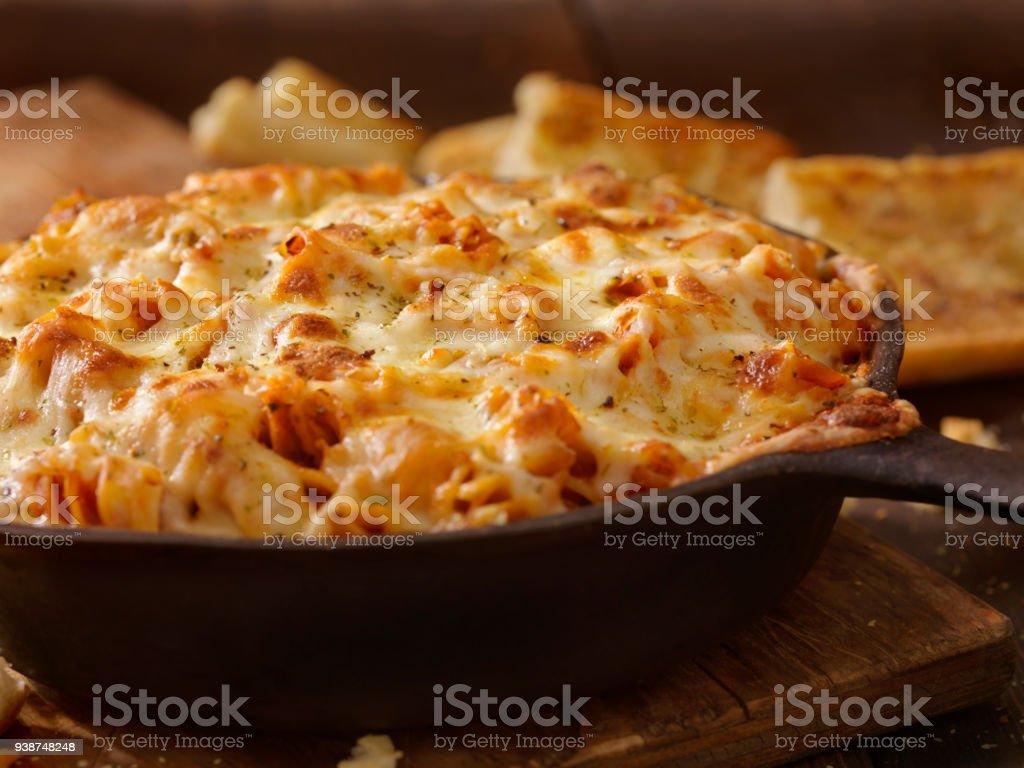 Kitschig gebackene Rotini Nudeln gebratene Tomaten und Knoblauch-Sauce mit Knoblauchbrot – Foto