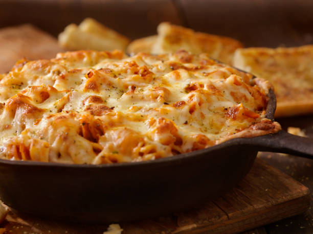 Cheesy Baked Rotini Pasta in Roasted Tomato and Garlic Sauce with Garlic Bread Cheesy Baked Rotini Pasta in Roasted Tomato and Garlic Sauce with Garlic Bread macaroni stock pictures, royalty-free photos & images
