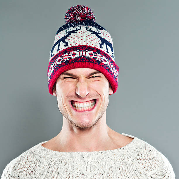 Cheesy Grin Portrait of cute young adult man wearing a sweater and a winter hat. Studio shot on the grey background.  clenching teeth stock pictures, royalty-free photos & images