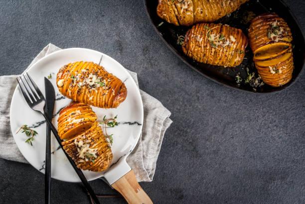 kitschig hasselback kartoffeln mit frischen kräutern - knoblauchkartoffeln stock-fotos und bilder