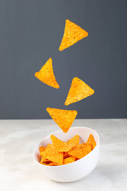 Cheesy tortilla chips or nacho levitate above the bowl,  vertical stock photo